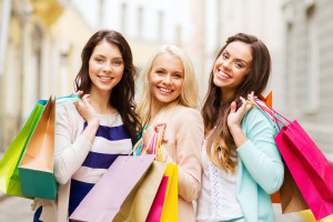 shopping and tourism concept - beautiful girls with shopping bag